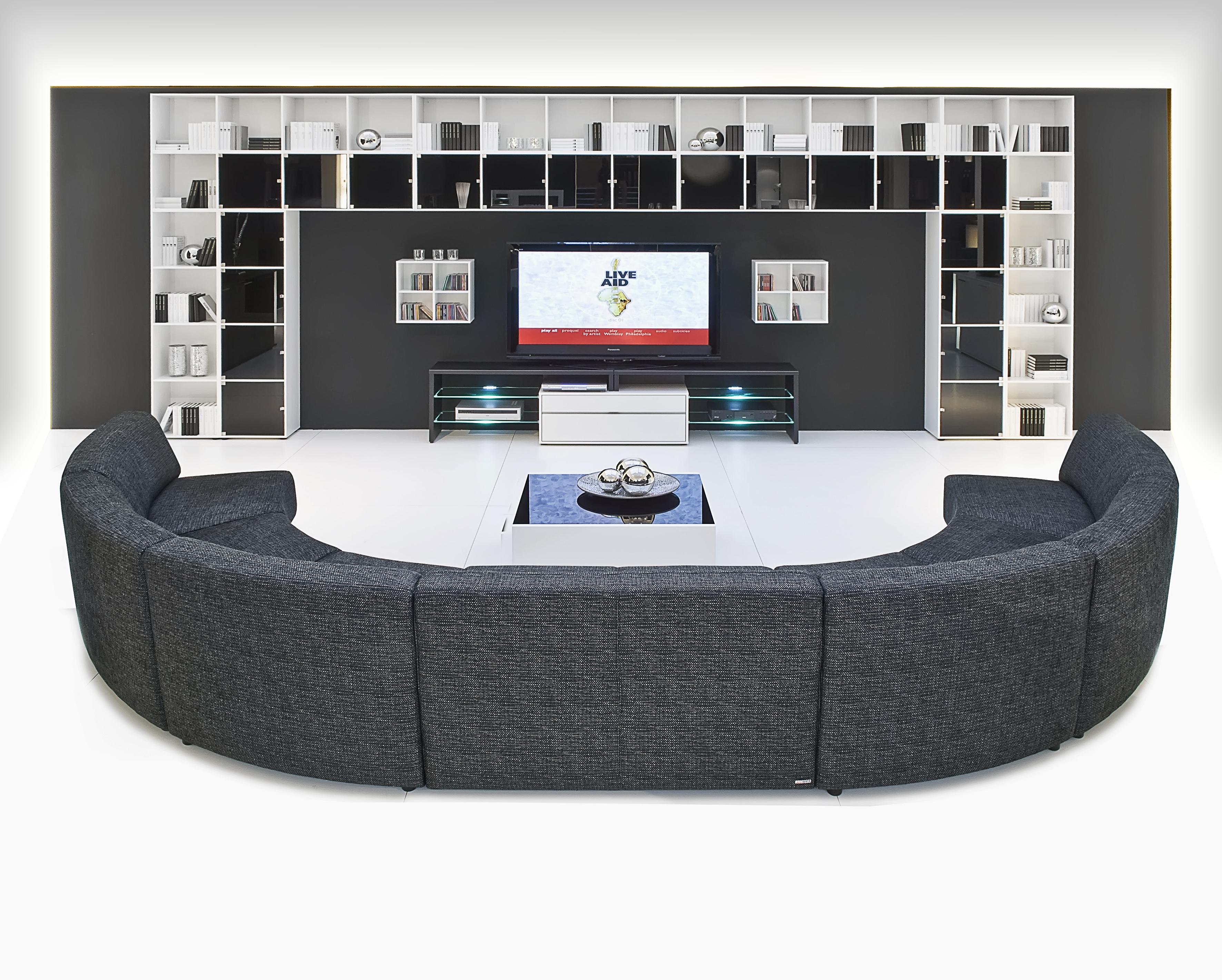 Sofá circular con estilo contemporaneo con un estante de pared balnco con negro con diversas subdivisiones
